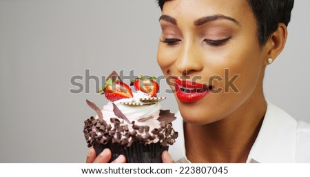 Black woman admiring a fancy dessert cupcake with chocolate and strawberries - stock photo