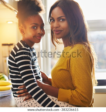 Black woman and her daughter smiling at camera looking happy - stock photo