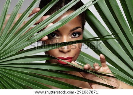 black woman between palm leaves - stock photo