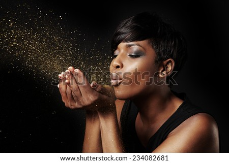 black woman blowing golden dust. Make a wish concept - stock photo
