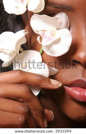 Black woman covering her eye with white orchid - stock photo