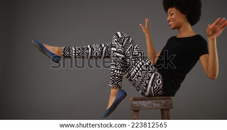 Black woman dancing on chair - stock photo