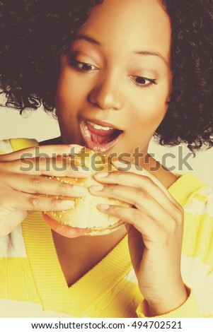 Black woman eating burger sandwich