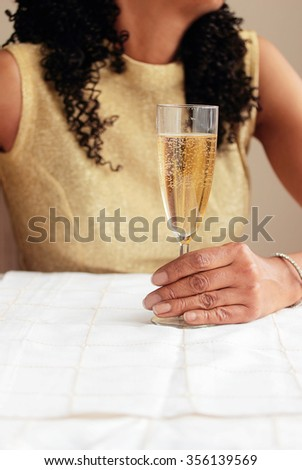 Black woman holding champagne glass in left hand - stock photo