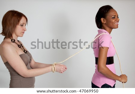 Black woman leading a bound White woman - stock photo
