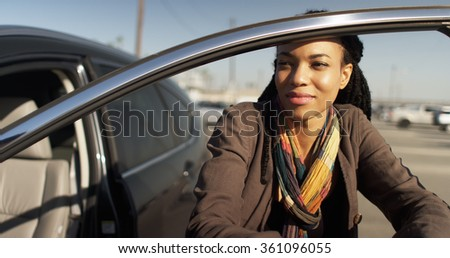 Black woman leaning against car door in parking lot - stock photo