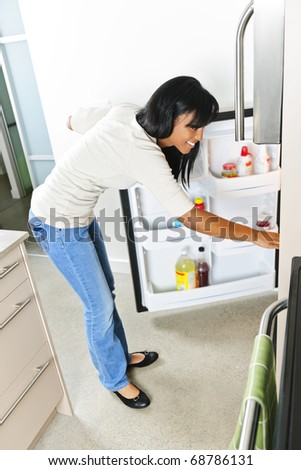 Black woman looking in fridge of modern kitchen interior - stock photo