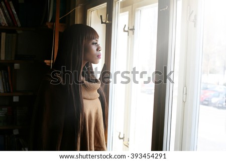 Black woman looking through the window. Sunlight races.