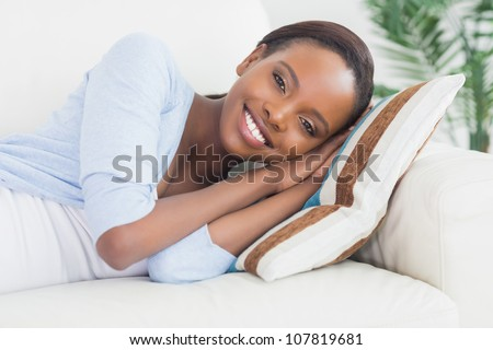 Black woman lying on side in a living room - stock photo