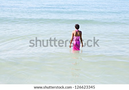 Black woman on a beach, walking into the sea wearing a bright pink sarong around her body while on vacations. - stock photo
