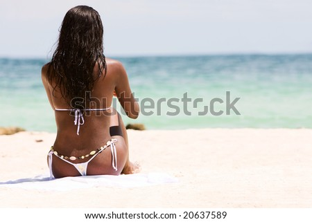 black woman relaxing on the beach while on vacation - stock photo