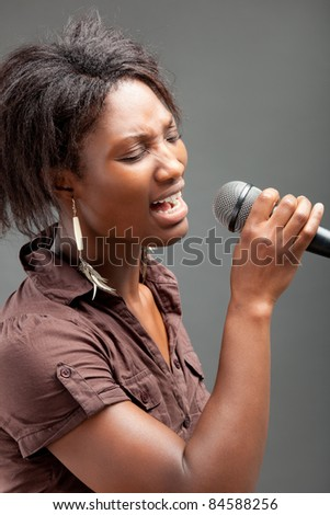 Black Woman Singing Into Microphone , on grey background - stock photo
