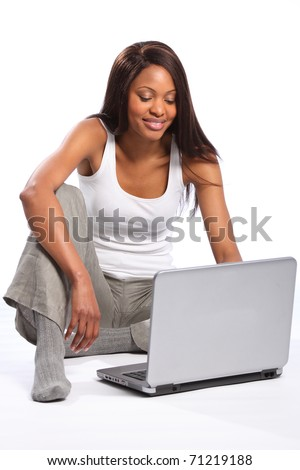 Black woman sitting on floor using laptop - stock photo