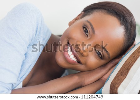 Black woman smiling while lying on side in a living room - stock photo