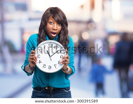 black woman surprised holding a clock - stock photo
