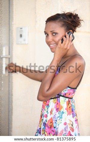 black woman wearing a summer dress coming home and calling - stock photo