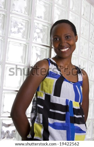 Black woman wearing colorful clothing posing against a glass background