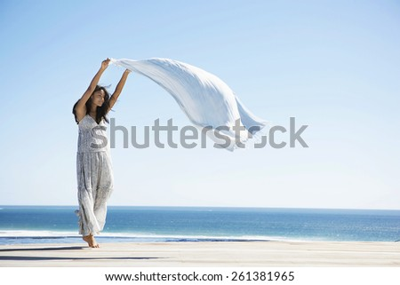 Black woman with a sarong at the beach feeling the wind - stock photo