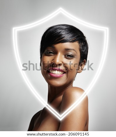 black woman with ideal skin behind the shield - stock photo