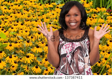 Black woman with the common wild flower known as a Blackeyed Susan. - stock photo