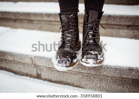 Black women's shoes on the stone steps covered by snow in the winter. - stock photo