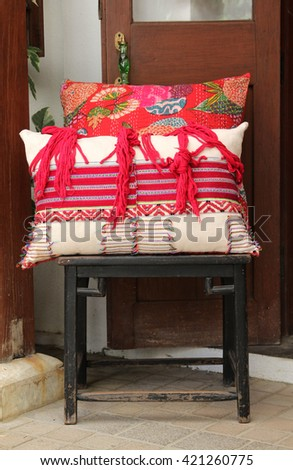 Black wooden chair with red pillow.
