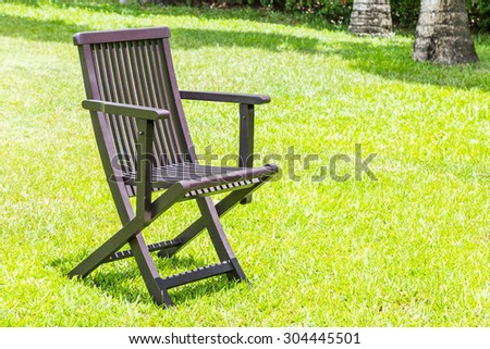 Black wooden chairs on the lawn green nature background