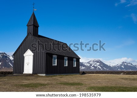 Black Wooden church and snow covered mountains in Budir, Iceland - stock photo