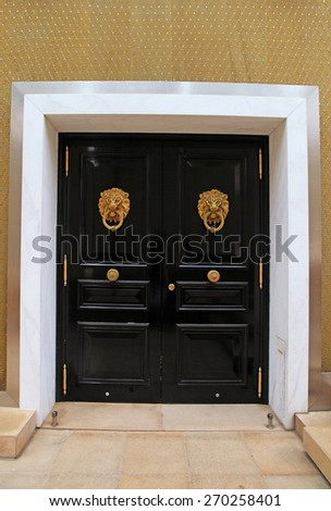 Black wooden door with knob in the shape of brass lion, Monaco - stock photo
