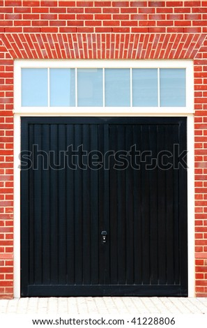 Black Wooden Garage Doors with a red brick surround - stock photo
