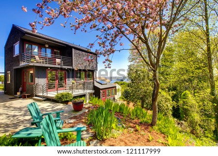 Black wooden modern house with spring backyard and two chairs. - stock photo