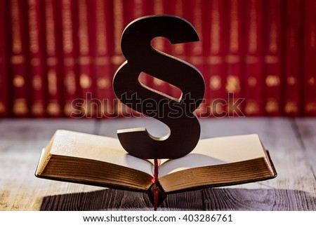 Black wooden paragraph the symbol of law in court library with legal codes. Law concept - stock photo