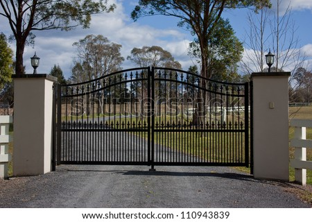 Black wrought iron entrance gates to rural property with trees and sky in background - stock photo