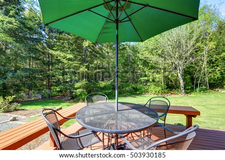 black wrought iron patio set with open umbrella in the backyard on a sunny day black wrought iron patio
