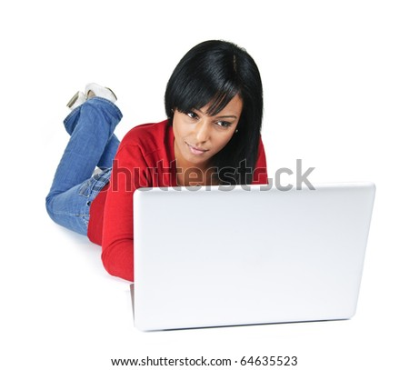 Black young woman typing on computer laying on floor - stock photo