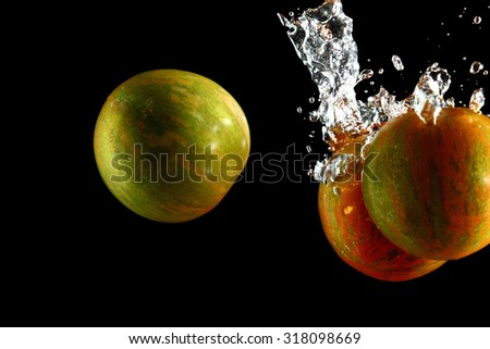 Black zebra tomatoes falling into water at black background - stock photo