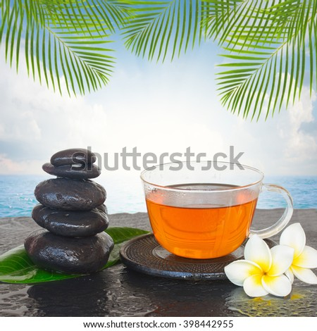 black zen stones with cup of tea and flowers by sea side - stock photo