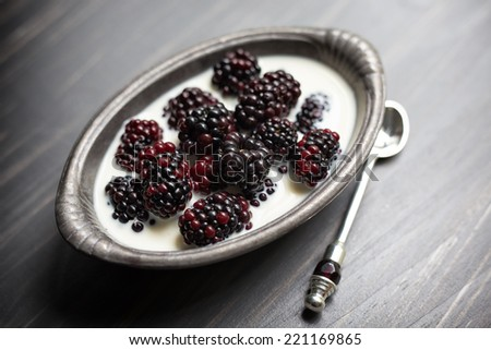 Blackberries and cream in a pewter dish with an antique sliver and garnet jeweled spoon.