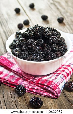 Blackberries in a bowl on wooden table - stock photo