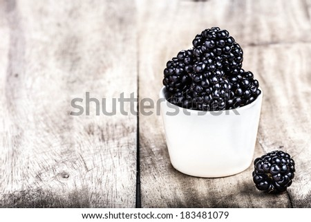 Blackberries in a white bowl on  bright wooden background close up with copyspace in country style. - stock photo