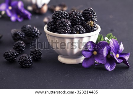 Blackberries in a white ceramic bowl on a black background with purple dried flowers - stock photo