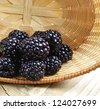 Blackberries in basket on a wooden table - stock photo