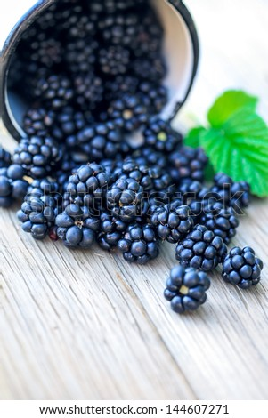 Blackberries in cup on a wooden table. Macro image. - stock photo