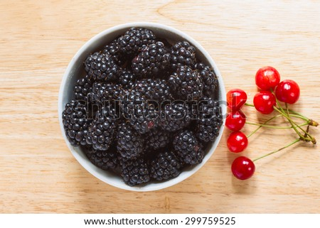 Blackberries in the ceramic bowl with cherries aside on the wooden plate