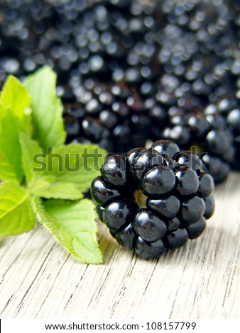 Blackberries on a wooden table and mint leaves - stock photo