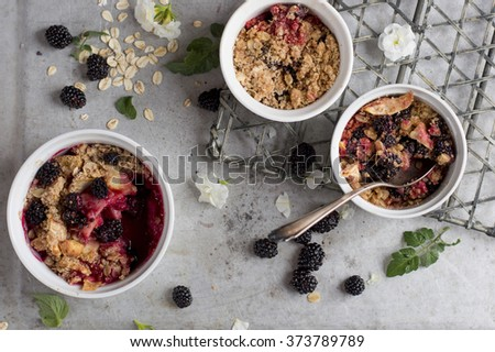 Blackberry and apple crumble dessert on vintage background, selective focus