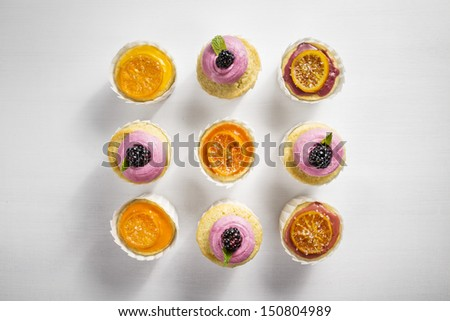 Blackberry Buttercream and Candied Clementine Glazed Cupcakes in White Cupcake Wrappers on a White Wood Natural Background - stock photo