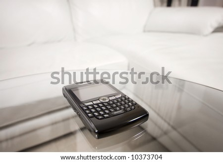 Blackberry on glass table in living room - stock photo
