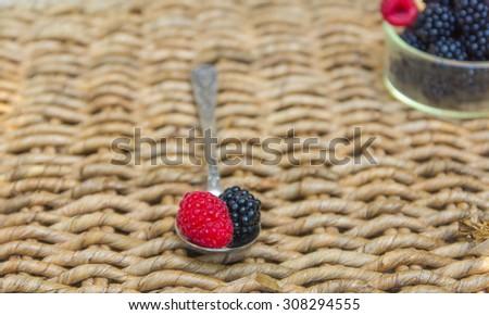 Blackberry on vintage metal spoon over wicker background.  - stock photo