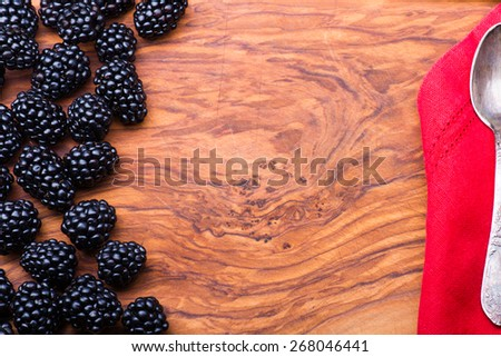 Blackberry on wood with lots copyspace and metal vintage spoon on red napkin - stock photo